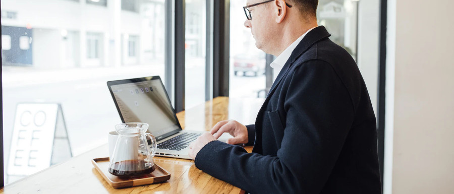man in a coffee shop using LinkedIn for business