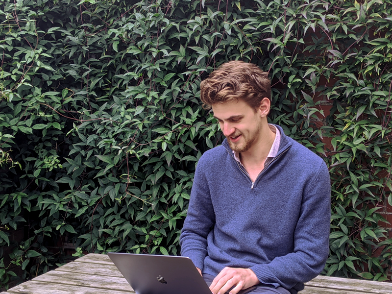 Cam Parry on a laptop outdoors