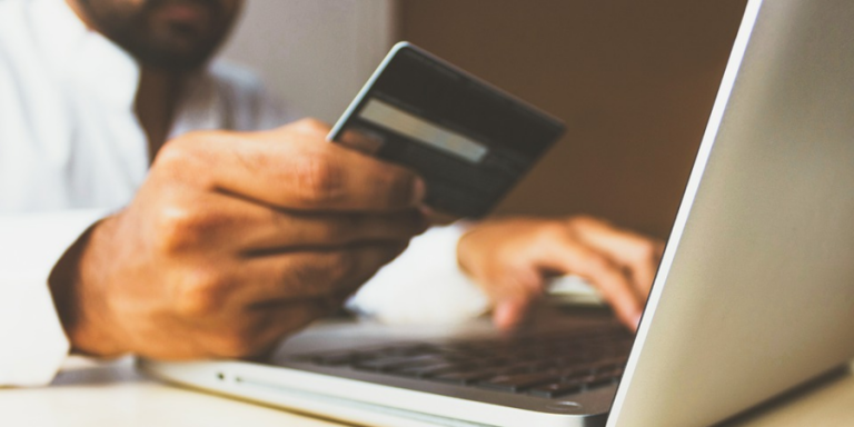 woman using a laptop and debit card for an online purchase