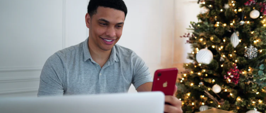 man using his phone for a Zoom Christmas party next to his Christmas tree